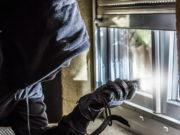 rapinatore con passamontagna davanti a finestra con piede di porco