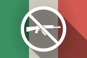 fucile d'assalto barrato su fondo di bandiera italiana: Auda contro il recepimento della nuova Direttiva armi