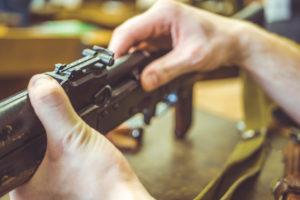 mani di armaiolo che smontano arma: corso licenza armi ed esplodenti di Conarmi