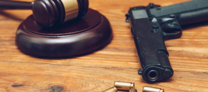 martello del giudice con pistola e quatto proiettili su tavolo di legno: botta e risposta Salvini - Anm sulla riforma della legittima difesa