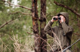 Cacciatore con fucile e binocolo nella foresta