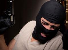 rapinatore appoggiato a una porta con pistola e passamontagna