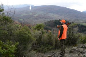 cacciatore con fucile in spalla e abbigliamento ad alta visibilità