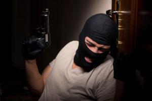 rapinatore appoggiato a una porta con pistola e passamontagna: riforma della legittima difesa