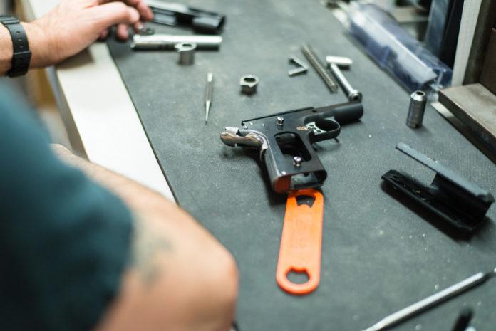 pistola smontata sul banco dell'armaiolo: corsi per licenze armi 2019