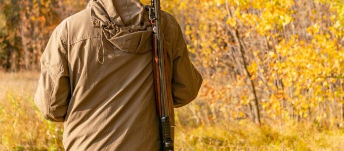 Specie cacciabili: cacciatore nel bosco, di spalle, con fucile a tracolla