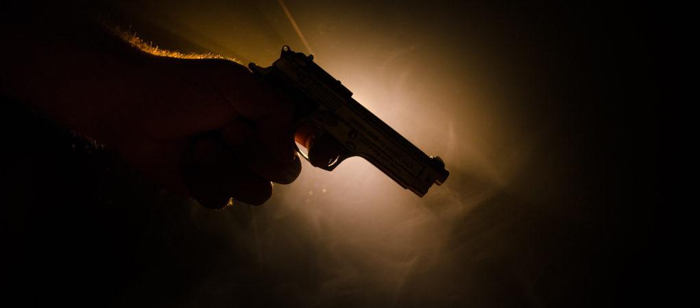 mano che impugna pistola: omicidi commessi con armi legalmente detenute