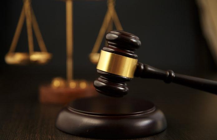 martello del giudice davanti a bilancia: condanne penali e porto d'armi