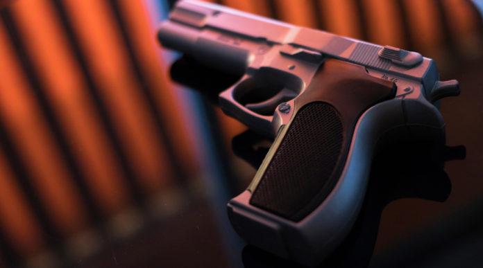 legittima difesa, pistola su tavolo di vetro