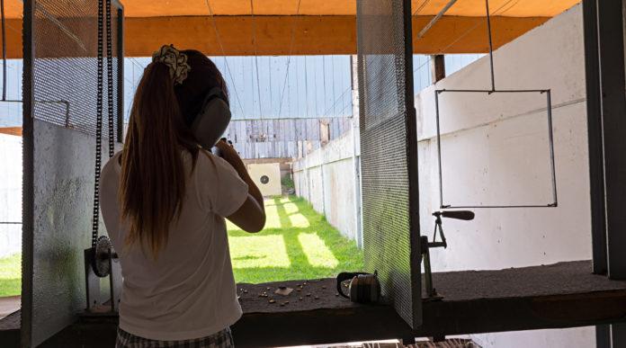 ragazza di spalle mentre imbraccia arma in un poligono: scaricare dalle tasse la donazione per impianti sportivi
