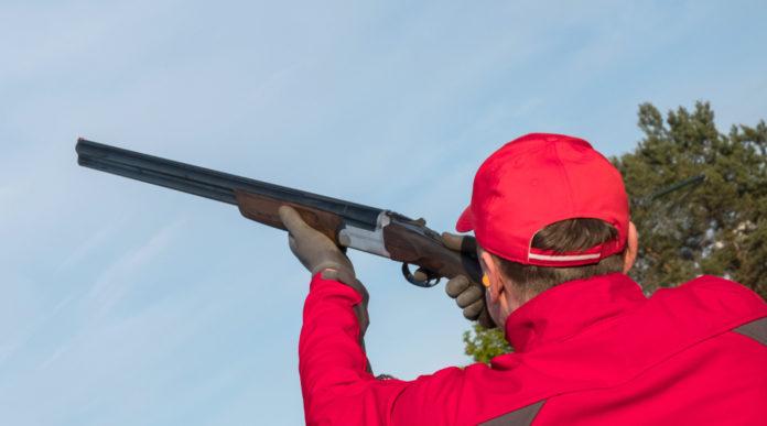 gara di tiro a volo per principianti: tiratore vestito di rosa spara a piattello