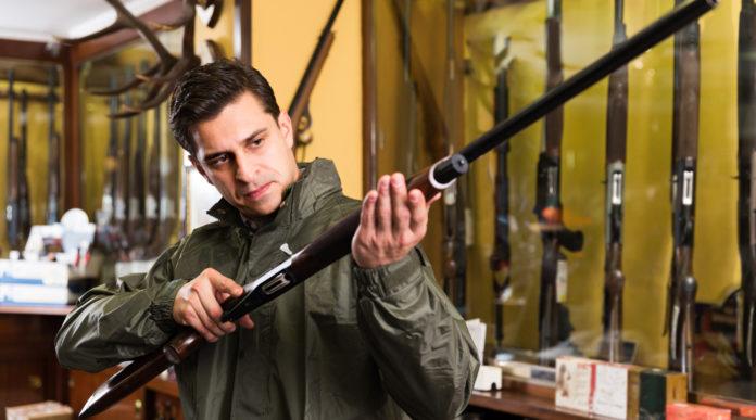 leggi sulle armi: venditore di armi in armeria presenta fucile