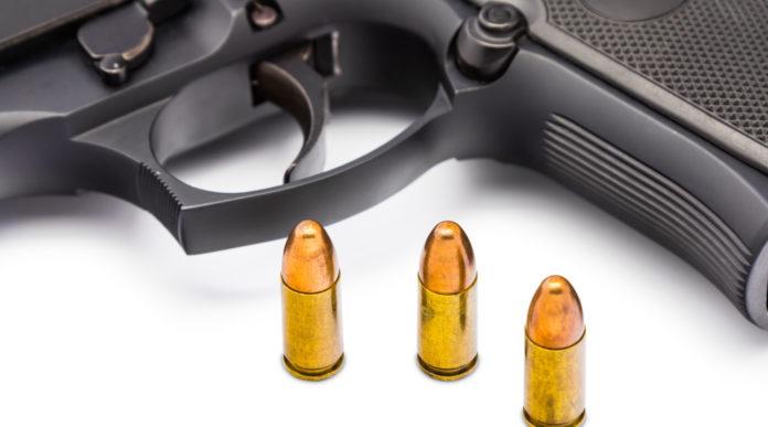 pistole 9 mm in America: tre proiettili calibro 9 mm davanti a una pistola