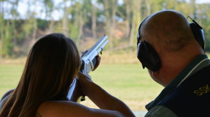 munizioni in piombo per il tiro: tiratrice affiancata da istruttore, di spalle