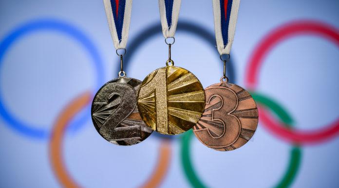Carte olimpiche per Tokyo 2020: medaglie d'oro, argento e bronzo davanti ai cerchi olimpici