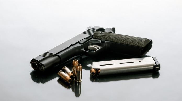 Diffusione delle armi: pistola 1911 con caricatore estratto e munizioni a fianco