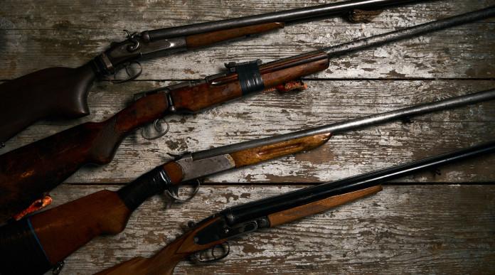 Armi in collezione: quattro fucili su tavolo di legno